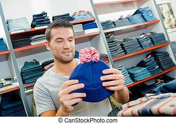 Man looking at bobble hat in shop