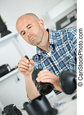 man looking at broken photographic lense