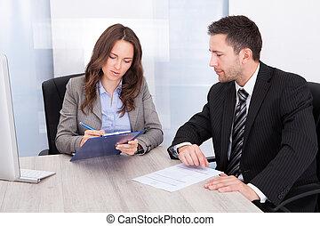 Man Looking At Businessman Writing
