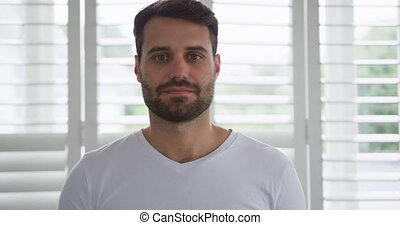 Man looking at camera in a comfortable home 4k