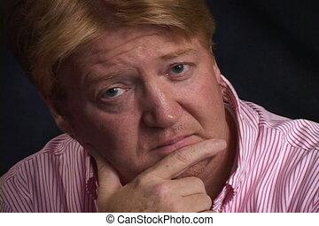 Man Looking At Camera - Man in a pin-striped shirt puts his...