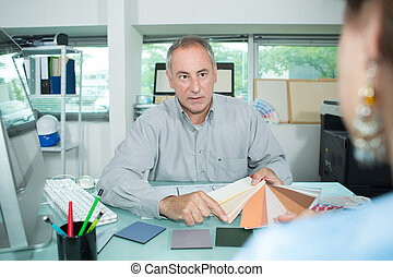 man looking at color swatches in designer office