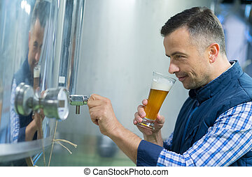 man looking at dark craft beer