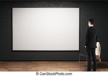 Man looking at empty billboard