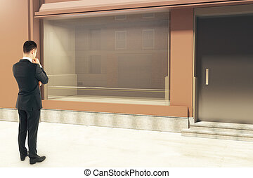 Man looking at empty storefront - Thoughtful businessman...