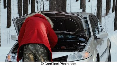 Man looking at engine of car. man repairing broken car. Winter Driving, trouble on a snowy country road.
