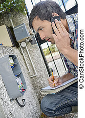 Man looking at exterior electrical box, on telephone taking...