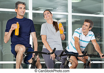 Man Looking At Friends With Juice Bottles On Spinning Bike