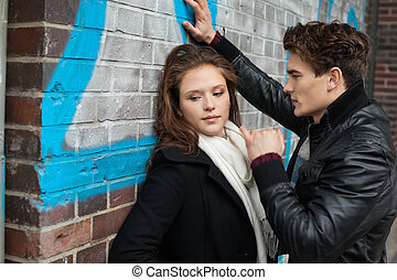 Man Looking At Girlfriend Leaning On Wall