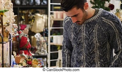 Man looking at goods on shelf - Handsome young man in jumper...