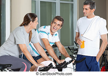 Man Looking At Happy Friends Exercising On Spinning Bike