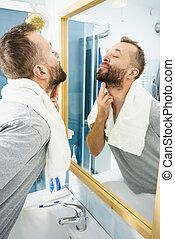 Man looking at his beard in mirror