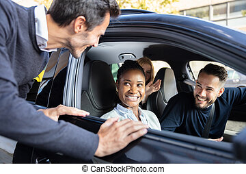 Man Looking At His Happy Friends Sitting In Car