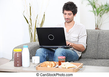 Man looking at his laptop before breakfast
