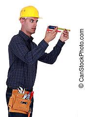 Man looking at his measuring tape surprisingly