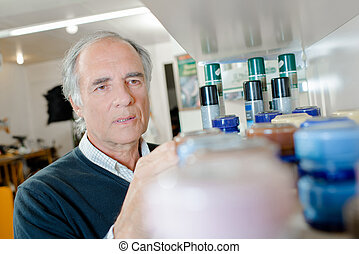 Man looking at jars on shelf