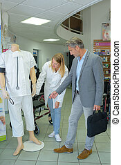 Man looking at medical uniform in a shop