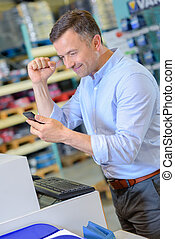 Man looking at mobile phone making gesture of success