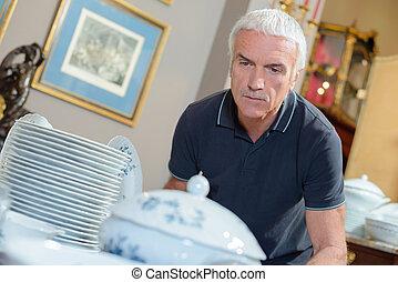 Man looking at porcelaine crockery