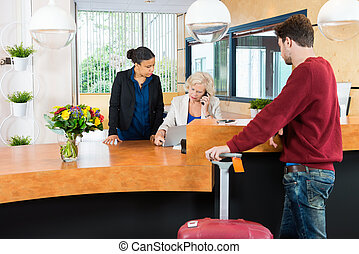 Man Looking At Receptionists In Hotel