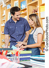 Man Looking At Saleswoman In Store