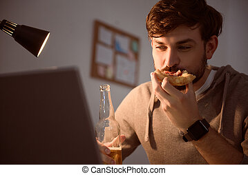 Man looking at screen and eating pizza