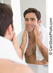 Man looking at self in mirror in the bathroom