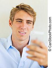 Man looking at smart phone, Texting