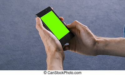 Man looking at smart phone with green screen