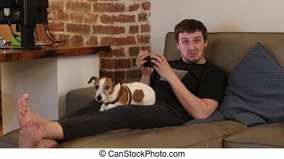 Man looking at smartphone sitting on sofa with dog. Guy...