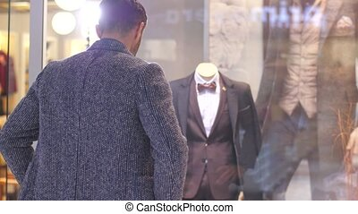 Man looking at suit in a shop window