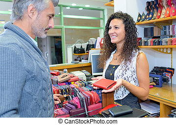 Man looking at wallets in a shop