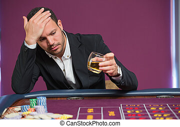 Man looking at whiskey glass