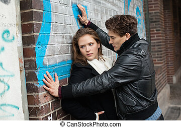 Man Looking At Woman Leaning On Wall