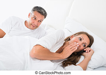 Man Looking At Woman Talking On Mobile Phone