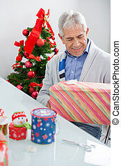 Man Looking At Wrapped Christmas Present
