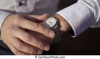 Man looking at wrist watches outdoors