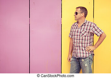 man looking away standing near the wall.