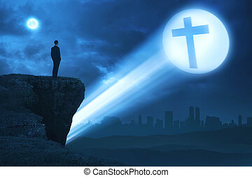 Man looking bright cross on the edge of cliff