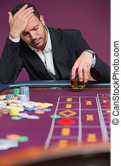 Man looking dejected at roulette table