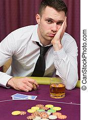Man looking depressed at poker table