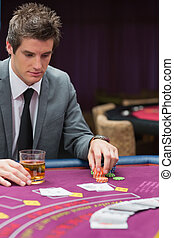 Man looking down at poker table