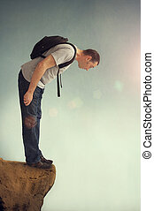 man looking down from a rocky ledge with backpack