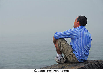Man looking fog - Man sitting on a rocky shore, looking at...