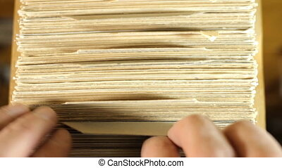Reader searching the book in the card index of the library catalog