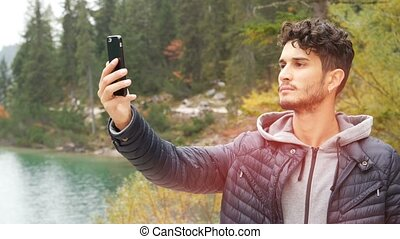 Man looking for reception at lake with smartphone