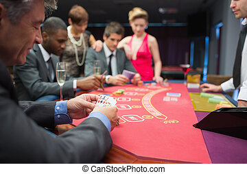 Man looking happily at his poker hand