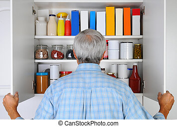 Man Looking in His Pantry - Closeup of a mature male looking...