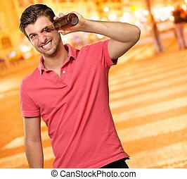 man looking inside an empty bottle