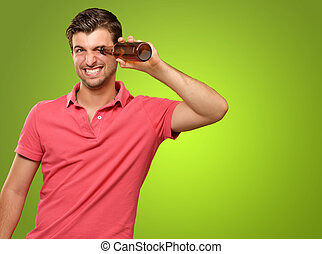 man looking inside an empty bottle isolated on green...